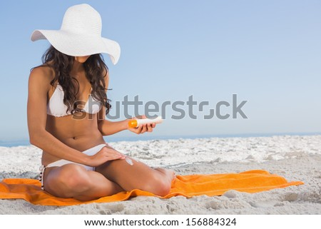 Attractive dark haired woman on the beach applying sun cream while sitting on her towel - stock photo