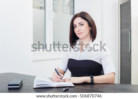 attractive dark-haired woman wearing a black and white blouse sitting at the desk in the office.business woman at the table with notebook and pen