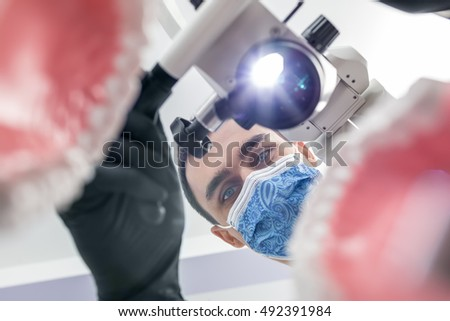 Attractive dentist looks through the blurry tooth jaw models. Man holds a glowing dental microscope with right hand. He wears black gloves and a blue medical mask with patterns. View from the bottom.
