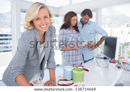 Attractive designer looking at the camera while a couple is choosing colours - stock photo