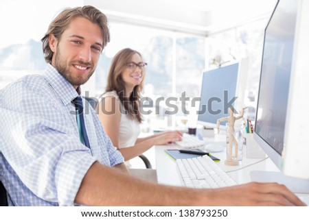 Attractive designers at work at their desk in modern office - stock photo