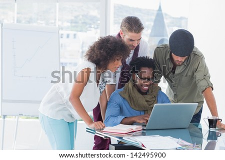 Attractive designers working in office at desk and using laptop - stock photo