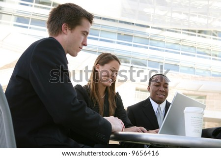 Attractive diverse business team working on laptop computer - stock photo
