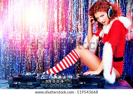 Attractive DJ girl mixing up some Christmas cheer. Disco lights in the background. - stock photo