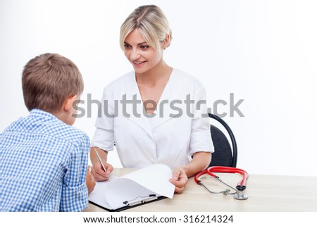 Attractive doctor is talking with a boy. They are sitting at the table and smiling. The woman is looking at the child happily and writing down some notes. Isolated on background - stock photo
