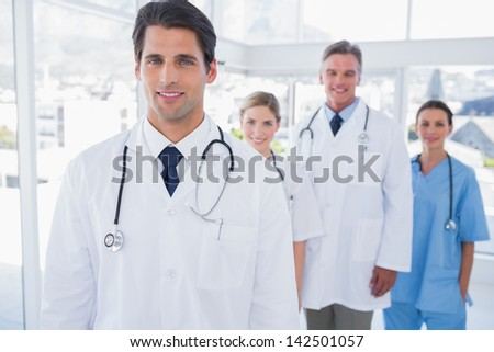 Attractive doctor standing in front of his team