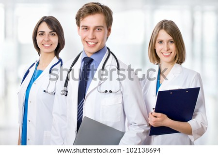 Attractive doctor with his young colleagues - stock photo