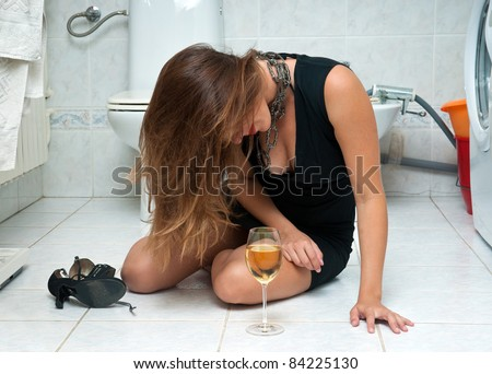 attractive drunk woman in her bathroom with glass of wine - stock photo