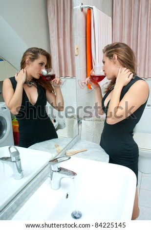 attractive drunk woman in her bathroom with glass of wine