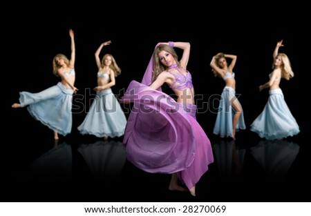 Attractive east girls dances isolated on a black background - stock photo