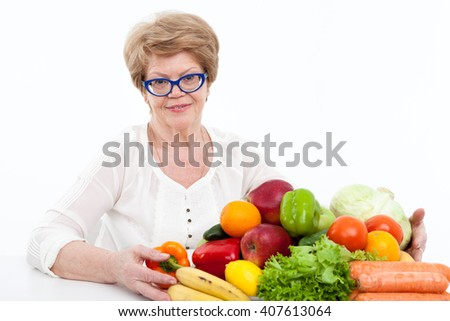 Attractive elder Caucasian woman embracing fresh vegetables and fruits on table, white background - stock photo