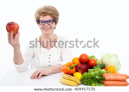 Attractive elder Caucasian woman showing red apple, fresh vegetables and fruits are on table, white background - stock photo