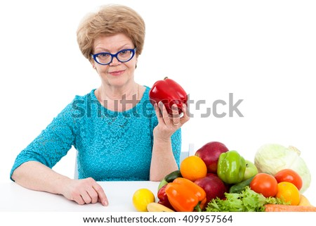 Attractive elder Caucasian woman showing red sweet pepper, fresh vegetables and fruits are on table, isolated on white background - stock photo