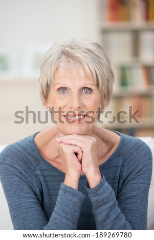 Attractive elderly blue-eyed woman sitting looking directly into the camera on a sofa at home with an alert attentive expression - stock photo