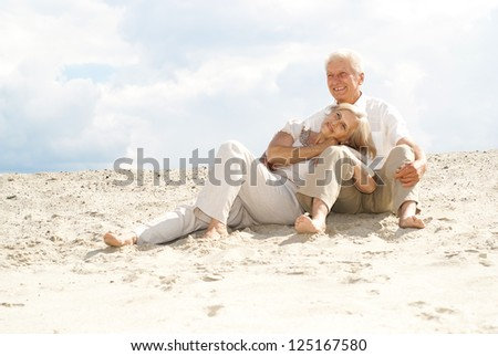 Attractive elderly couple went to the beach to enjoy the sea breeze - stock photo