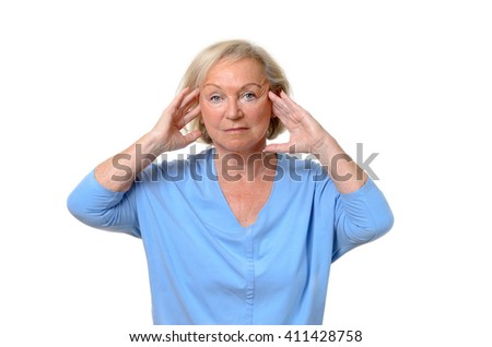 Attractive elderly lady suffering from a headache holding her hands to her temples as she stares glumly at the camera in a health and wellness concept, upper body isolated on white - stock photo