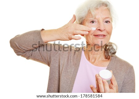 Attractive elderly woman applying lotion to her face - stock photo