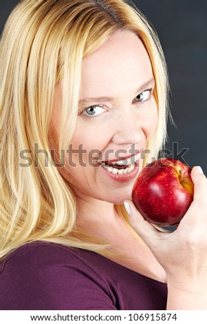 Attractive elderly woman eating a red apple