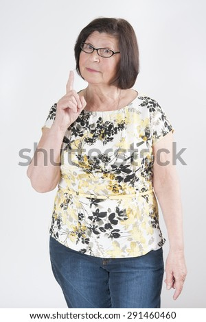 Attractive elderly woman threatens with a finger.  - stock photo