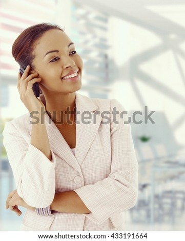 Attractive, elegant afro american businesswoman with mobile phone. Smiling, standing, warm colors. Copyspace. - stock photo