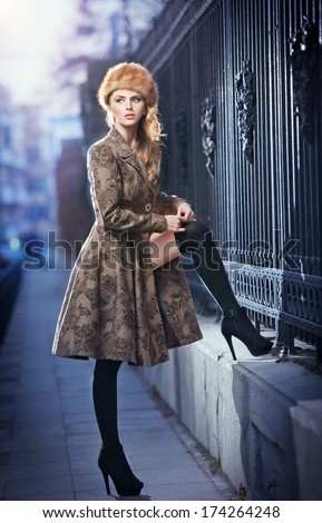 Attractive elegant blonde young woman wearing an outfit with Russian influence in urban fashion shot. Beautiful fashionable young girl with long legs and fur cap posing on street - stock photo