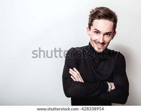 Attractive elegant man in black golf posing on light gray background. - stock photo