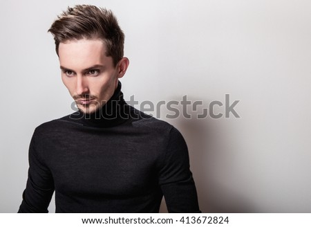 Attractive elegant man in black sweater posing on light gray background. - stock photo