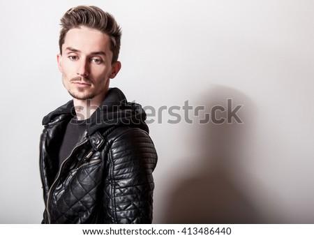Attractive elegant man in stylish black leather jacket posing on light gray background. - stock photo