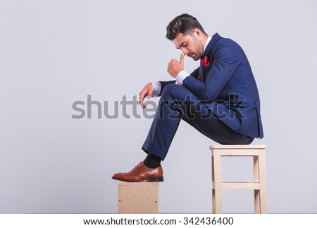 attractive elegant man in suit sitting in studio looking down while touching his nose - stock photo