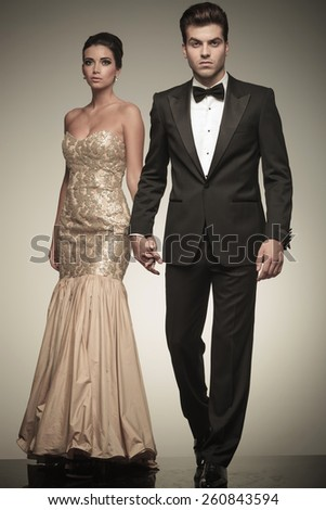 Attractive elegant man walking on studio background while holding his lover hand. - stock photo