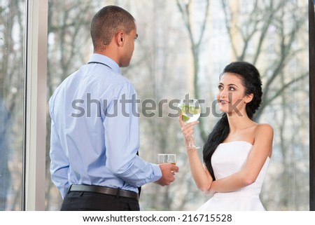 Attractive elegant young couple drinking wine. beautiful couple talking near window - stock photo
