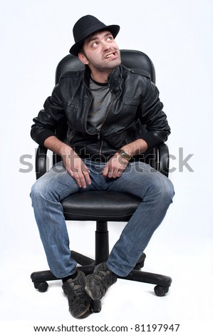 attractive emotional macho man in leather jacket sit in leather chair,caucasian young man, isolated over white