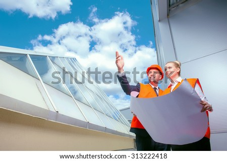 Attractive engineer is explaining his ideas about building to his female colleague. The man is pointing his arm sideways. The woman is looking there and holding blueprint. They are smiling - stock photo