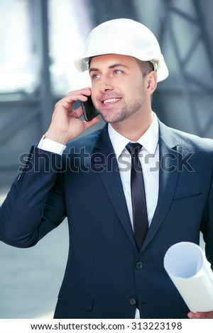 Attractive engineer is talking the phone with his customer. He is holding a blueprint and smiling. His project was approved. The man is wearing a suit and a hardhat - stock photo