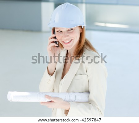Attractive engineer on phone smiling at the camera - stock photo