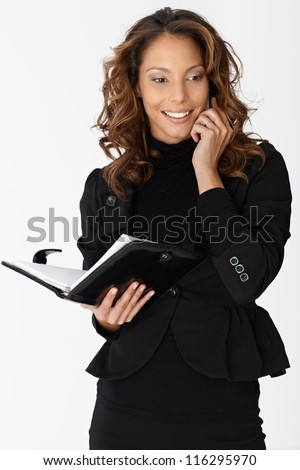 Attractive ethnic businesswoman talking on mobile phone, smiling, holding organizer in hand.