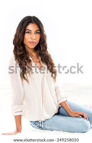 Attractive ethnic young woman sitting with white background - stock photo