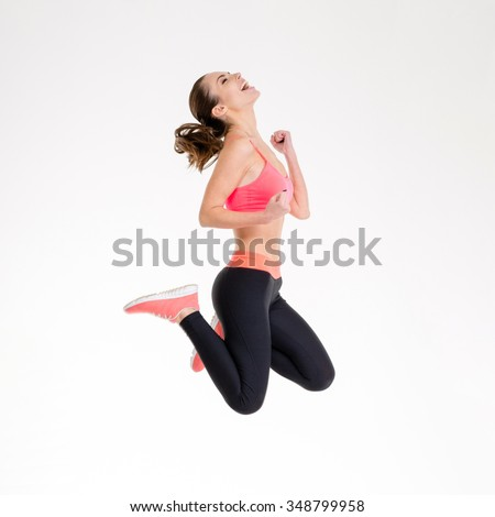 Attractive excited fitness girl in sportwear jumping of joy isolated over white background - stock photo