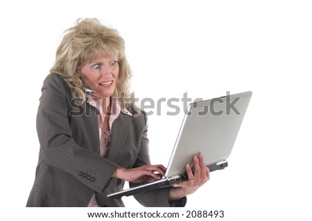 Attractive executive business woman standing up juggling a laptop computer and a cell phone.