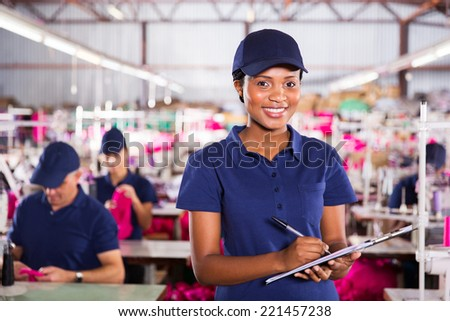 attractive factory quality controller holding a clipboard - stock photo