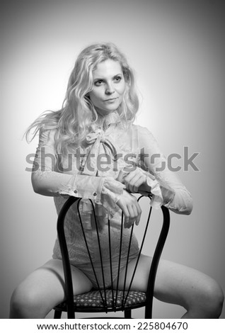 Attractive fair hair model with in elegant nude blouse sitting provocatively on chair, studio shot. Fashion portrait of a sensual blonde woman in classic blouse with long sleeves and ribbon on chair  - stock photo
