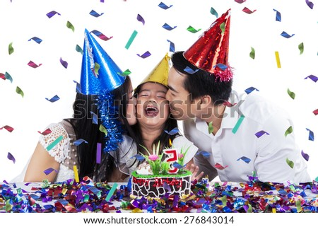 Attractive family celebrating birthday party while wearing birthday cap and kiss the girl, isolated on white - stock photo