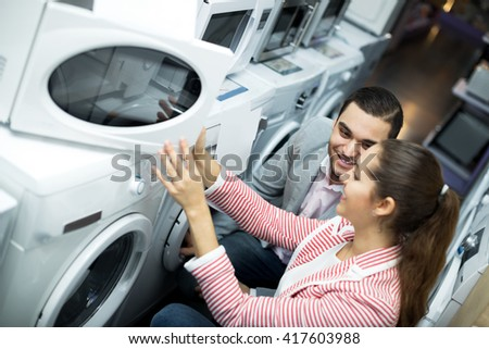 Attractive family couple choosing new microwave in supermarket. Focus on the man