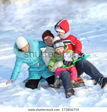 Attractive family having fun in a winter park - stock photo