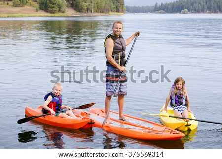 Attractive family kayaking and paddle boarding together on a beautiful lake - stock photo