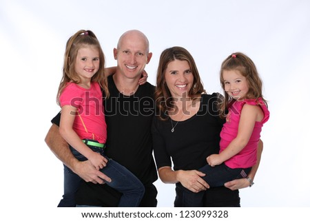 Attractive family of four, with mother, father and two daughters, wearing pink and black in studio on white isolated background - stock photo