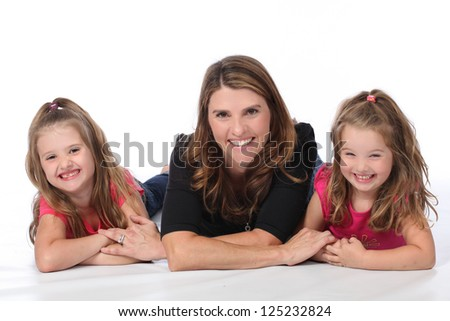 Attractive family of three, with mother and two daughters, wearing pink and black in studio on white isolated background - stock photo