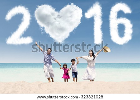 Attractive family running together on the beach while celebrating new year with cloud shaped numbers 2016 - stock photo