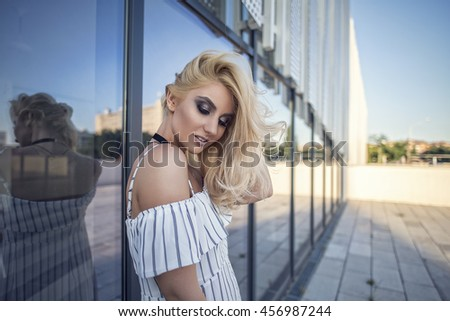 Attractive fashion blonde woman posing street style in white dress - stock photo