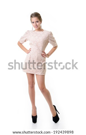 Attractive fashion girl dressed in elegant beige dress, full length portrait over white - stock photo